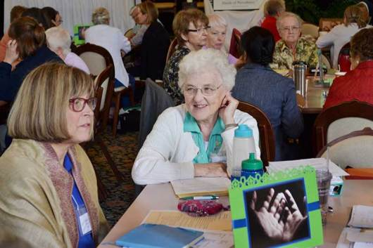 Sister Janice Smith (left) and Sister Patty Fillenwarth during table discussion time. (photo by Amy Miranda)