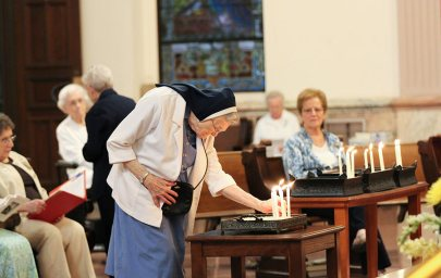 Sister Marian Brady places her candle as a chapter delegate during the opening ritual. (photo by Amy Miranda)