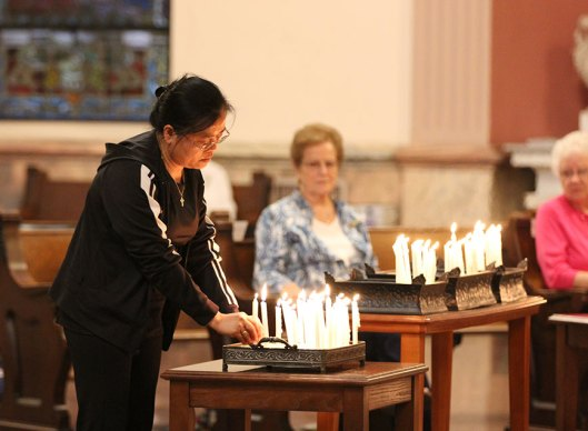 Sister Su-Hsin Huang places her candle during the opening ritual. (photo by Amy Miranda)