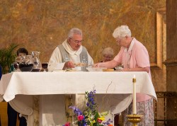 Father Dan Hopcus is assisted in preparing the communion bowls by Sister Joseph Fillenwarth
