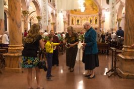 Sister Jenny Howard receives a rose from Mary Cassell and her son Guerin following the ceremony