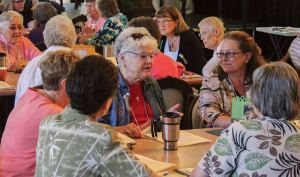 Article author Sister Rosemary Nudd, center, in conversation with sisters and associates at her table on the first day of Chapter, including Providence Associate Teresa Clark at right.