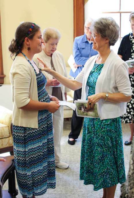 During a prayer ritual within the ceremony, Emily receives a blessing from Sister Jeanne Hagelskamp.