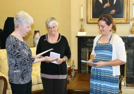 Director of Postulants Sister Marsha Speth presents Emily with the key to her new home in the formation community at Saint Mary-of-the-Woods as Sister Denise Wilkinson looks on.