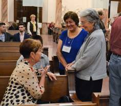 Adriana Estringel and her companion Sister Barbara Bluntzer, standing, chat with other associates.