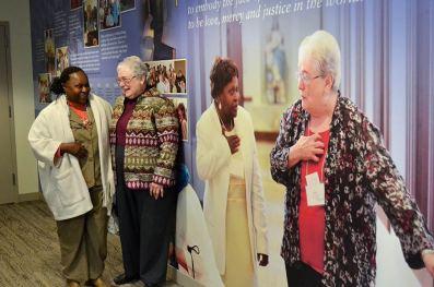 Providence Associate Sarian Bouma and her companion Sister Marie McCarthy pose near a photo of themselves on the new Providence Associate timeline wall