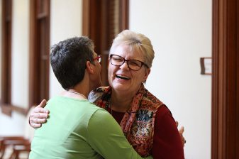 Providence Associate Maria Price congratulates new Co-Director Sister Sue Paweski with a hug.