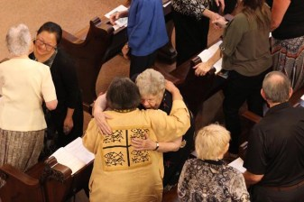 Silver jubilarians Sisters Kate Smith and Pat Linehan exchange a hug at the sign of peace.