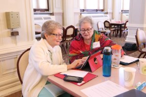 Using and ipad to share information are Sisters Betty Hopf and Mary Ann DeFazio.