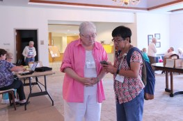 Sister Marie McCarthy checks out something on Sister Evelyn Ovalles' phone.