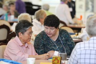 Sisters Celeste Tsai and Judith Cervizzi discuss a point at their table.