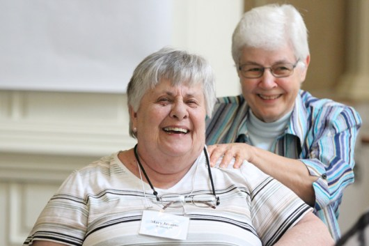 Sister Mary Jeanine Schubert receives a shoulder massage from Sister Mary Jo Piccione during a break in a long stretch of meeting.