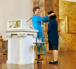 """It's at the novitiate stage that a woman in formation adds """"Sister"""" before her name. Sister Dawn blesses with holy water a plain, white and silver cross, and presents it to Sister Teresa Kang."""