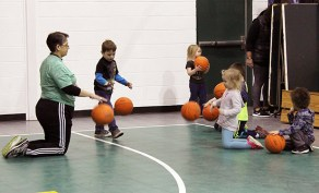 Sister Joni Luna (left) works with students at St. Patrick's School on the art of dribbling.