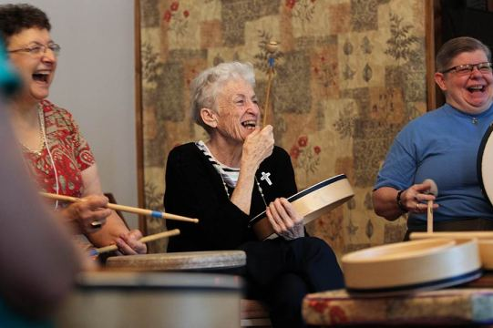 Sister Ann Stephen Stouffer, center, laughs during a drumming circle with Providence Associate Marilyn Rausch joining her at left and volunteer Stacy Pierce at right.