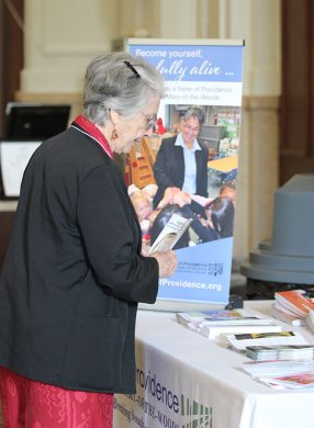 Sister Barbara Bluntzer checks out a table full of marketing material for the Congregation to be shared with others.