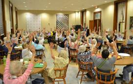 Sisters and associates raise their hands in song during Sunday evening's music therapy demonstration.