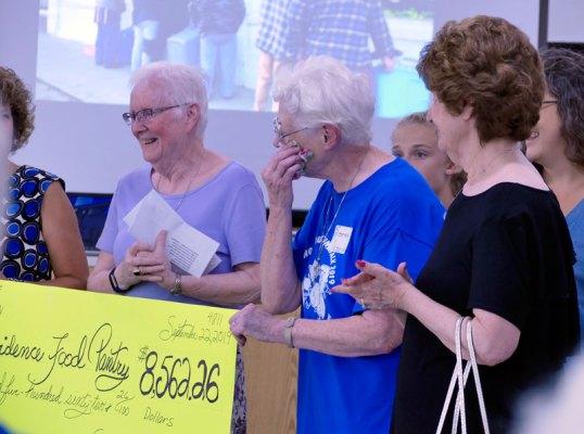 Sister Joan Slobig (left) presents Sister Joseph Fillenwarth proceeds from the Saint Mary's Village fun run/walk.