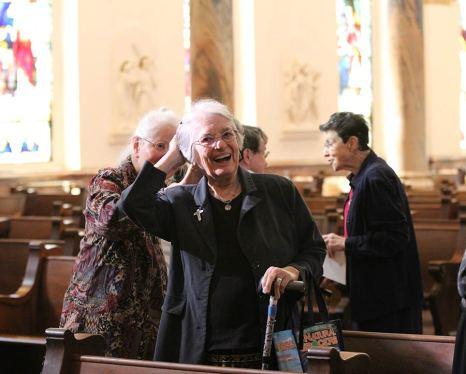 Sister Barbara Ann Bluntzer smiles as another sister fixes her hair after Mass