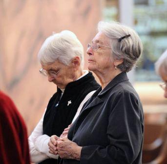 Sister Margaret Norris and Barbara Bluntzer in prayer