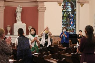 The sisters gathered applaud the newly professed sisters as Mass ends