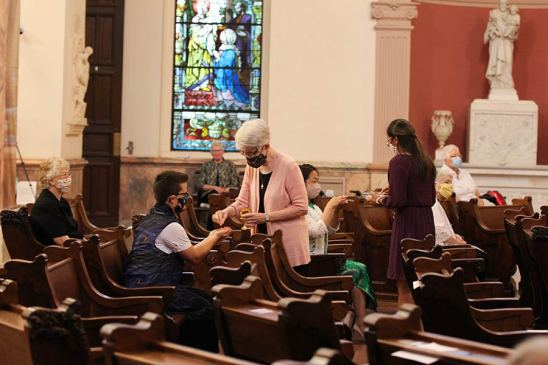 Sisters Marsha Speth and Jessica Vitente give communion to the newly professed sisters.
