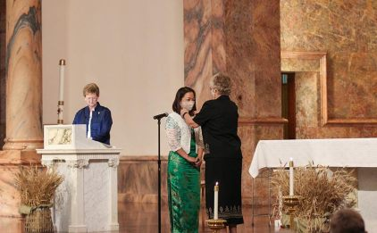 Sister Teresa receives her white cross, the symbol of a professed Sister of Providence, from Sister Jenny Howard and Sister Dawn Tomaszewski looks on