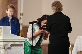 Sister Teresa kisses the Bible during the vow ceremony
