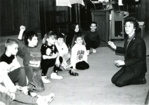 Sister Gloria, right, sitting on the floor and working with a line of elementary students sitting opposite her.