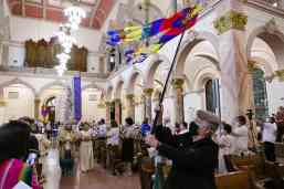 Sister Jody O'Neil waves a banner in the procession as Sister Joni Luna and Sister Jessica Vitente enter to profess their vows.