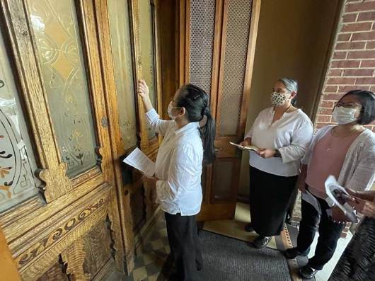 Leslie Dao knocks on the door of Providence Hall seeking entrance with the Sisters of Providence Congregation as Sister Joni Luna looks on.