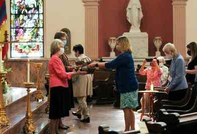 Sisters Jeanne Hagelskamp and Dawn Tomaszewski receive commitment cards from new Providence Associate Tanya Pongracz.