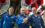 """En el fondo las instalaciones en el Cosmódromo de Baikonur, en Kazajstán, Expedición 37/38: El ingeniero de Vuelo Michael Hopkins de la NASA (izquierda), Comandante de la Soyuz Oleg Kotov (centro) y el ingeniero de vuelo Sergey Ryazanskiy (derecha) Cierran sus manos en frente de los motores de la 1ra etapa del cohete Soyuz-FG el 20 de septiembre, ya que se completó un """"examen de control"""" en la inspección final de su nave espacial Soyuz TMA-10M. Hopkins, Kotov y Ryazanskiy se están preparando para su lanzamiento el 26 de septiembre, hora de Kazajstán, para comenzar una misión de cinco meses y medio en la Estación Espacial Internacional. Foto: NASA/Victor Zelentsov"""