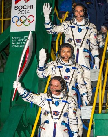 Expedición 38, el Comandante de la Soyuz Mikhail Tyurin de Roscosmos sosteniendo la antorcha olímpica, el Ingeniero de Vuelo Koichi Wakata de la Agencia de Exploración Aeroespacial de Japón, y el ingeniero de vuelo Rick Mastracchio de la NASA en parte superior, dicen adiós antes de subir al cohete Soyuz TMA-11M para el lanzamiento, el jueves 7 de noviembre de 2013, en el Cosmódromo de Baikonur en Kazajstán. La antorcha olímpica tiene una visita de cuatro días a la Estación Espacial Internacional. Tyurin, Mastracchio y, Wakata pasarán los próximos seis meses a bordo de la Estación Espacial Internacional. Crédito de la imagen: (NASA / Bill Ingalls)