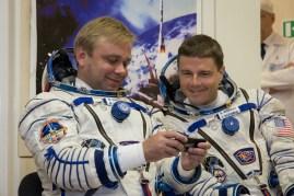 """En el cosmódromo de Baikonur, en Kazajstán, El comandante de la Soyuz Maxim Suraev de la Agencia Federal Rusa del Espacio, Roscosmos (izquierda) y el ingeniero de vuelo de la NASA Reid Wiseman, ven fotos de su familias en un teléfono inteligente el 16 de mayo antes de un ensayo general """"Comprobaciónes de ajuste"""" en su nave espacial Soyuz TMA-13M. Crédito de la imagen: NASA / Victor Zelentsov."""