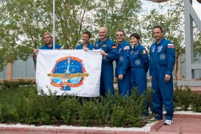 24 de mayo de 2014. Afueras del Museo Korolev en el Cosmódromo de Baikonur, en Kazajstán, Expedición 40/4, principales miembros de la tripulación Maxim Suraev de la Agencia Espacial Federal Rusa (Roscosmos, a la izquierda), el ingeniero de vuelo Reid Wiseman de la NASA (segundo por la izquierda) y Alexander Gerst de la Agencia Espacial Europea (tercero desde la izquierda); exhiben la bandera de su equipo insignia Soyuz, durante las ceremonias tradicionales previas al lanzamiento. Con ellos están los miembros de la tripulación de respaldo Terry Virts de la NASA (tercero desde la derecha), Samantha Cristoforetti de la Agencia Espacial Europea (segundo desde la derecha) y Anton Shkaplerov (a la derecha). Crédito de la imagen: NASA / Victor Zelentsov.