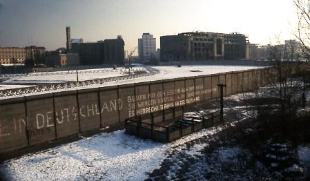 """Muro de Berlín: Potsdamer Platz en noviembre de 1975 mirando hacia el sureste en dirección a Stresemannstraße. Hacia la izquierda inmediata se ve la parte trasera de la Cámara de los Lores de Prusia en abandono, los edificios del medio son en su mayoría de la Stresemannstraße: como el edificio Stresemannstraße 128 (con muro y torre de vigilancia en el techo), a la derecha """"Haus Vaterland"""". Al frente del muro esta la entrada a la estación de metro de Potsdamer Platz (abandonado en el momento de la imagen). Foto: Edward Valachovic."""