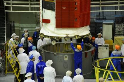 18 de marzo de 2015: Luego de que los diseñadores han completado su inspección, la nave Soyuz TMA-16M (módulo orbital) es integrada en el segmento PkhO que la conecta con el cohete portador Soyuz-FG. Foto: S.P. Korolev/RSC Energia.