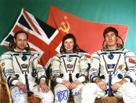 Fotografía autografiada de la tripulación de la Misión Juno: Helen Sharman del Reino Unido (centro), flanqueada por los cosmonautas soviéticos Anatoli Artsebarski (izquierda) y Serguéi Krikaliov (derecha), con las banderas de sus países como fondo, poco antes de su vuelo espacial a bordo de la nave Soyuz TM-12 el 18 de mayo de 1991 en Baikonur, Unión Soviética. Foto: GCTC.