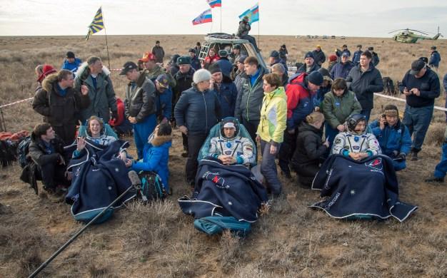 La astronauta de la NASA Kate Rubins, (izq), el cosmonauta ruso Anatoli Ivanishin de Roscosmos, (cent), y el astronauta Takuya Onishi de la Agencia de Exploración Aeroespacial de Japón (JAXA) sentados sillas fuera de la nave espacial Soyuz MS-01, momentos después de que aterrizaran en un área remota cerca la ciudad de Zhezkazgan. Crédito de la imagen: NASA / Bill Ingalls.