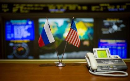21 de Octubre de 2016: Banderas de las dos naciones representadas en la Expedición 49, al fondo los monitores del Centro de Control de Misión Koroliov en Moscú, Rusia, mientras la Soyuz MS-02 se aproxima al acoplamiento con la estación Espacial Internacional. Crédito de la imagen: NASA / Joel Kowsky.