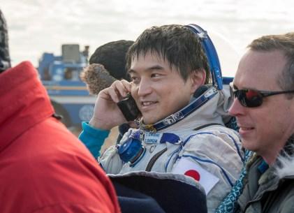 El astronauta japonés Takuya Onishi habla por un teléfono satelital mientras es llevado a un puesto de revision médica, momentos después de que aterrizara junto a sus compañeros de tripulación en un área remota cerca la ciudad de Zhezkazgan. Crédito de la imagen: NASA / Bill Ingalls.