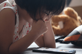 Little girl reading an ebook on a phone or tablet