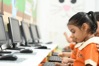 A teacher guiding a child to develop digital literacy skills