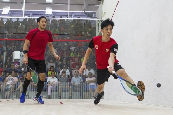Tang Ming Hong returns a shot to Elvinn Keo during their Singapore Open final