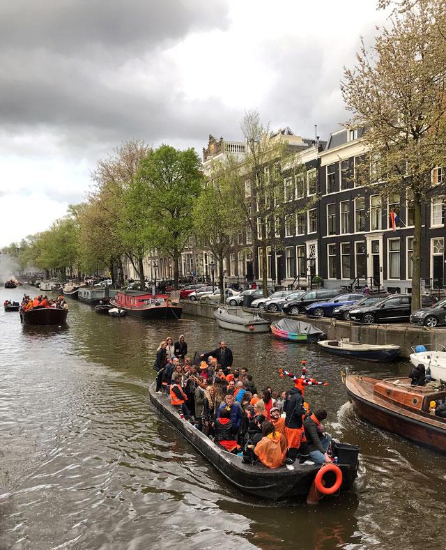 Barche in festa che girano sui canali di Amsterdam sono tipiche del Giorno del Re