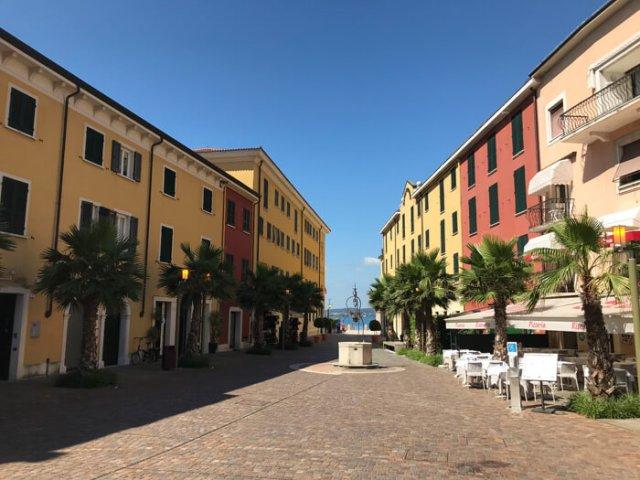 Piazza Castello colorata e con un pozzo apre il centro storico di Sirmione
