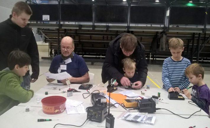 Pöydän ympärillä poika ja yksi isä rakentelemassa.
