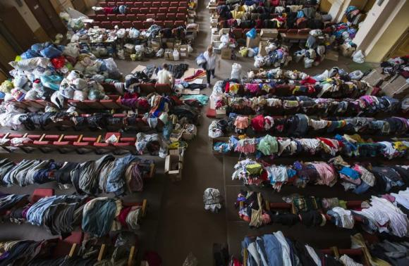 People walk among donated clothes at a former concert hall converted into a center for collecting humanitarian aid for refugees in Donetsk