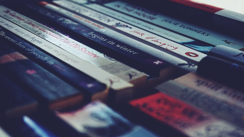Nonfiction and fiction editing. Spines of books lined up and out of focus. Stock photo: https://stocksnap.io